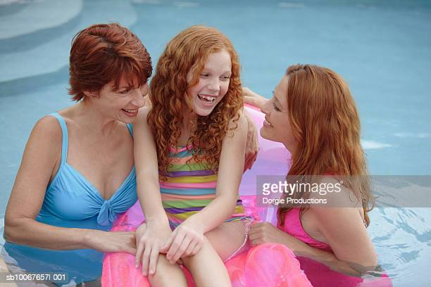mother, grandmother, and daughter (10-11 years) standing in swimming pool - 55 59 years stock pictures, royalty-free photos & images