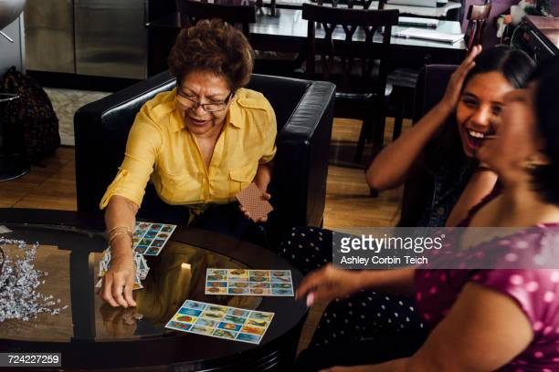 mother, grandmother and girl playing game - game night leisure activity stock pictures, royalty-free photos & images