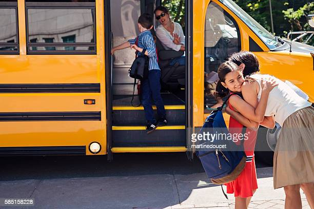 Mother greeting elementary age girl getting off school bus.