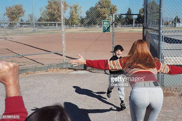 mother greeting son after baseball game - baseball mom stock pictures, royalty-free photos & images