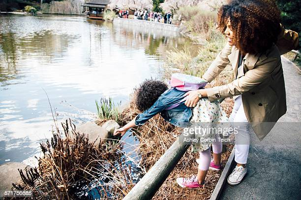 Mother gripping daughter stretching over guard rail to touch plant
