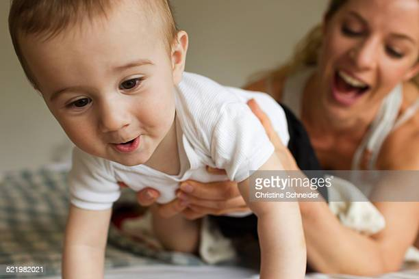 Mother guiding baby boy crawling on bed