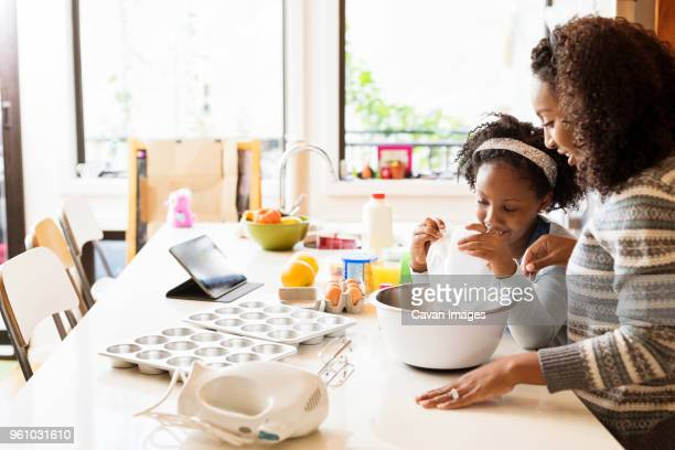 mother guiding daughter in making cupcakes - zakelijke kleding stock pictures, royalty-free photos & images