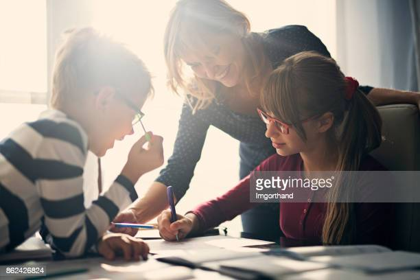 mother halping kids to do homework - genitori foto e immagini stock