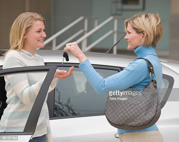 Mother handing car keys to teenaged daughter