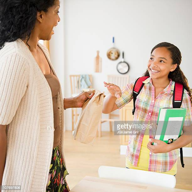 Mother handing daughter paper bag lunch