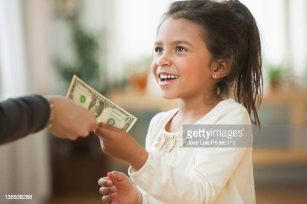 mother handing girl one dollar bill - family dollar stock pictures, royalty-free photos & images