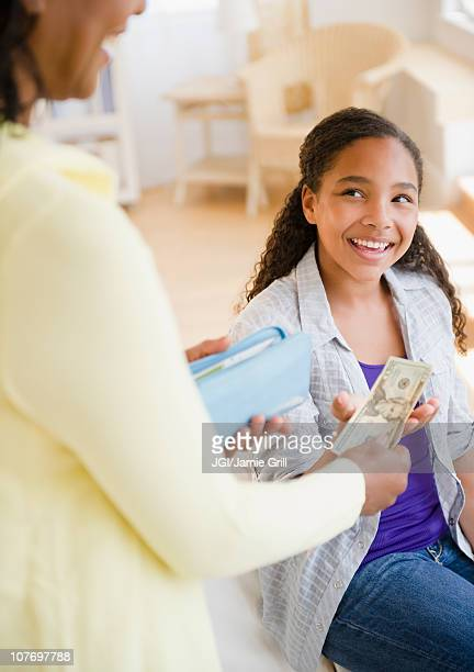 Mother handing money to daughter