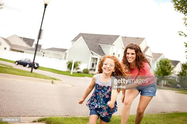 Mother Happily Chasing Her Daughter Outside on Summer Day