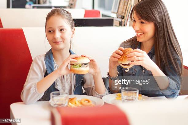 A mother having a burger in a diner with her daughter