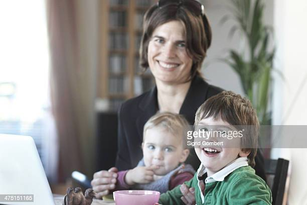 mother having breakfast with children before work - sigrid gombert stock pictures, royalty-free photos & images