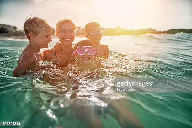 mother having fun splashing in sea waves - candid beach stock photos and pictures