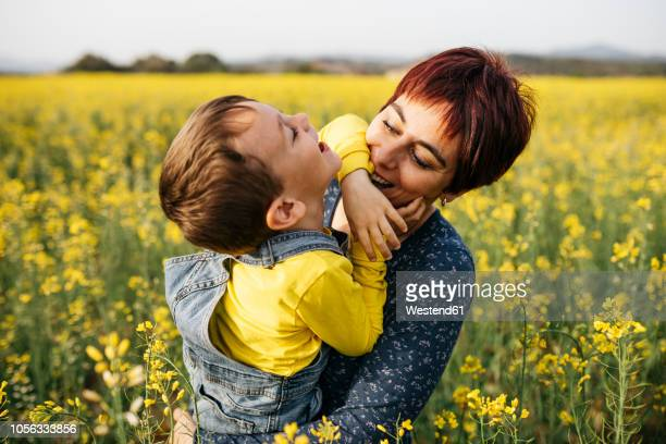 Mother having fun with her little son in a rape field