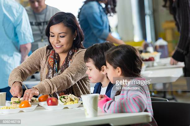 Mother having hot meal with children in community soup kitchen
