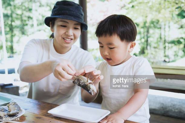 母は屋外焼き魚を食べる息子を助けるため
