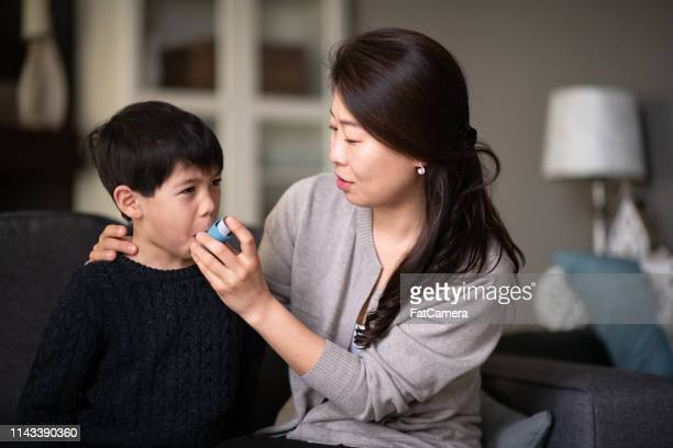 mother helping asthmatic son - asthma stock pictures, royalty-free photos & images