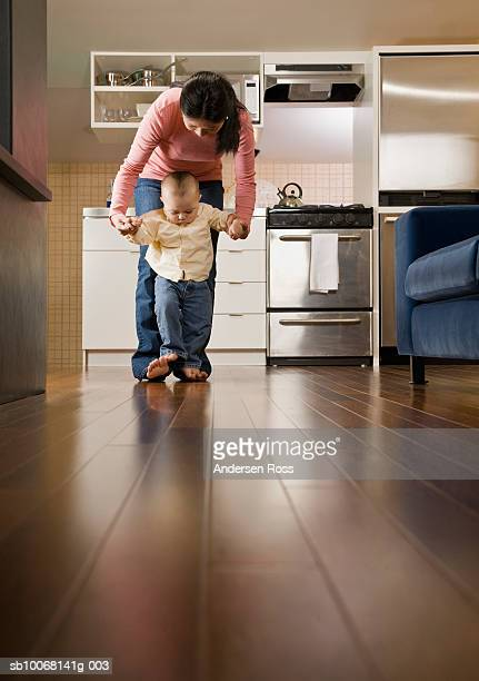 Mother helping baby boy (15-18 months) to walk