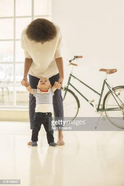 Mother helping baby boy walk in living room