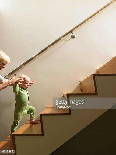 Mother helping baby boy walk up stairs