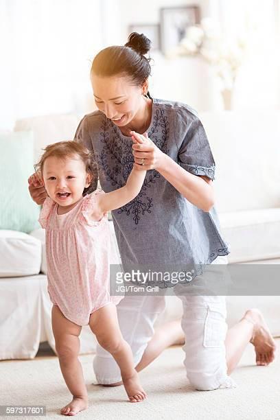 Mother helping baby daughter walk in living room