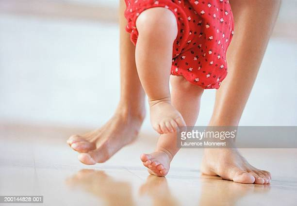 mother helping baby girl (9-12 months) to walk, low section - first occurrence stock pictures, royalty-free photos & images