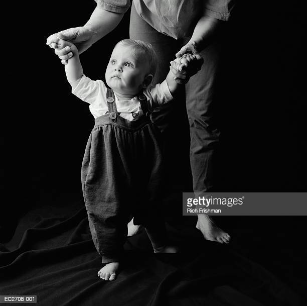mother helping baby son (9-12 months) to walk (b&w) - 12 23 months stock pictures, royalty-free photos & images