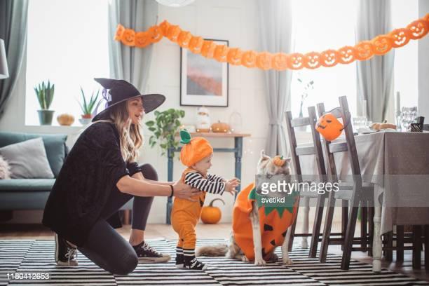 madre ayudando al bebé a caminar en halloween - halloween fotografías e imágenes de stock