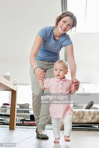 Mother helping baby to walk
