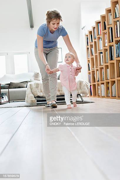 mother helping baby to walk - first occurrence stock pictures, royalty-free photos & images