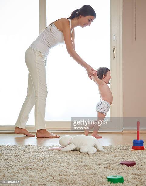 mother helping baby walk on living room floor - bent over babes stock pictures, royalty-free photos & images
