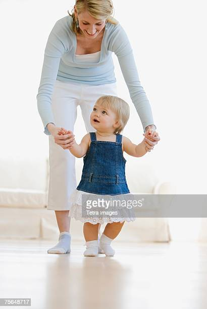 Mother helping baby walk