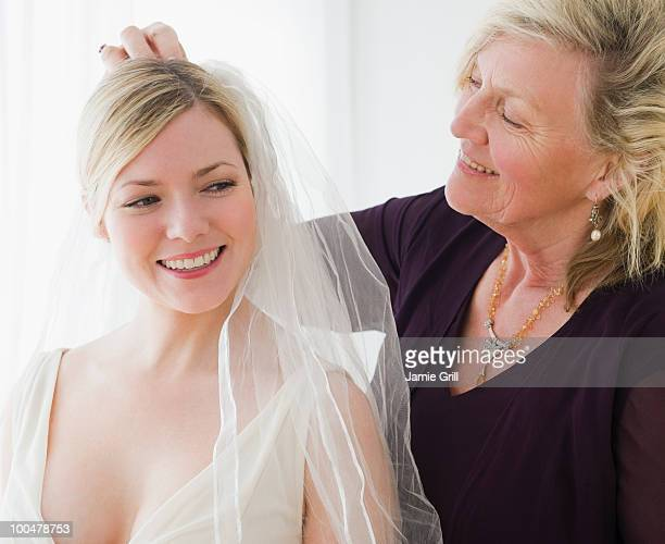 mother helping bride with veil - veil stock pictures, royalty-free photos & images