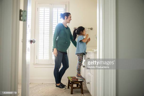mother helping daughter brush her teeth - parte del cuerpo humano fotos fotografías e imágenes de stock