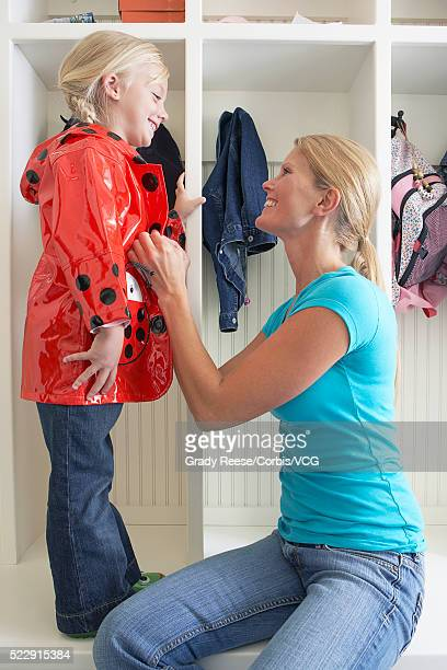 mother helping daughter dress - vintage raincoat stock photos and pictures