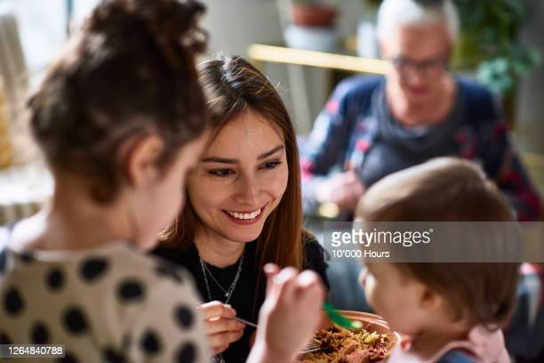mother helping daughter feed toddler - equipment stock pictures, royalty-free photos & images