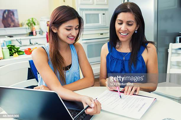 mother helping daughter fill out college applications in the kitchen - college application stock photos and pictures