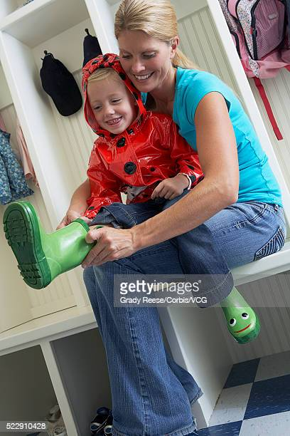 mother helping daughter get dressed - vintage raincoat stock photos and pictures