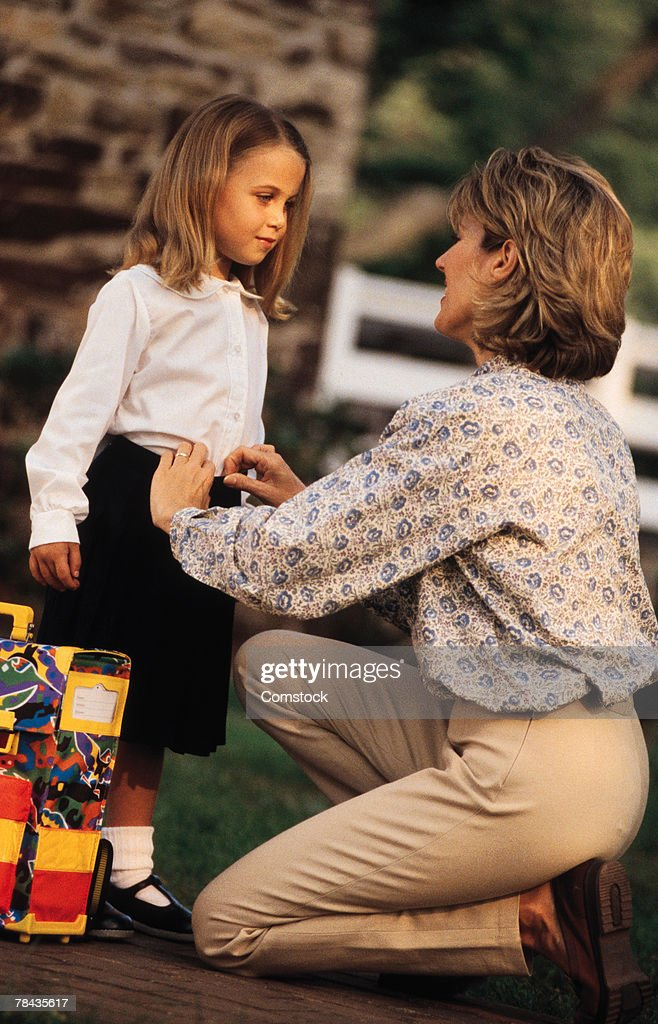 Mother helping daughter get ready for school : Stockfoto