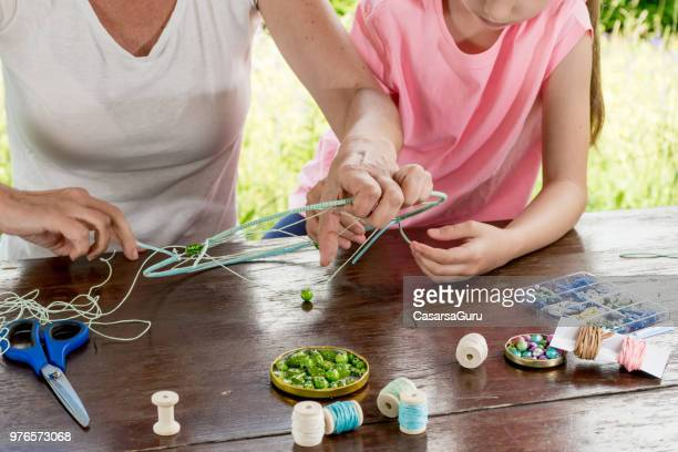 mother helping daughter making a dream catcher - dreamcatcher stock pictures, royalty-free photos & images