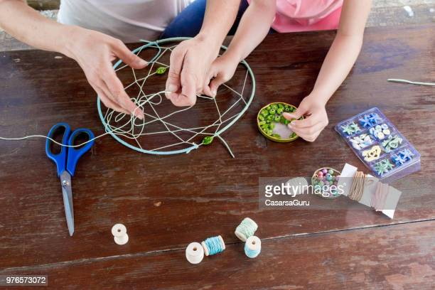 Mother Helping Daughter Making A Dream Catcher