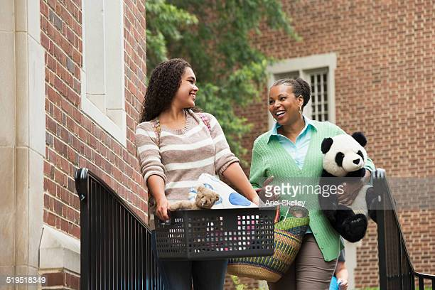 Mother helping daughter move into dormitory