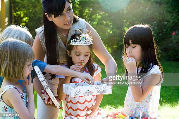 Mother helping daughter open gift at birthday party