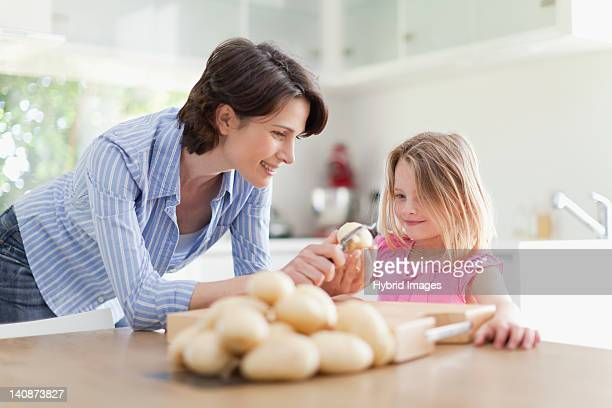 Mother helping daughter peel potatoes