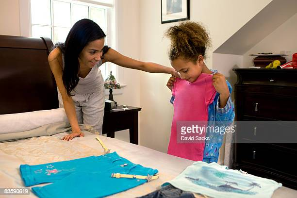 Mother helping daughter pick outfit