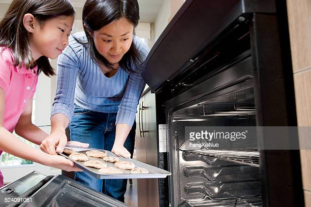 mother helping daughter put cookies in oven - richmond british columbia stock photos and pictures