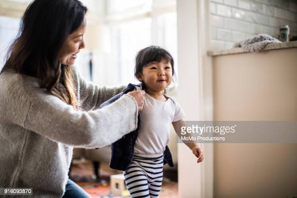 mother helping daughter (2yrs) put on coat - jaqueta - fotografias e filmes do acervo