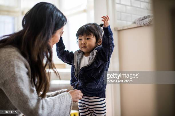 mother helping daughter (2yrs) put on coat - coat stock pictures, royalty-free photos & images
