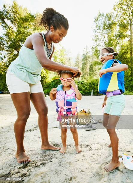 mother helping daughter put on goggles before playing in river on summer afternoon - beginnings stock pictures, royalty-free photos & images