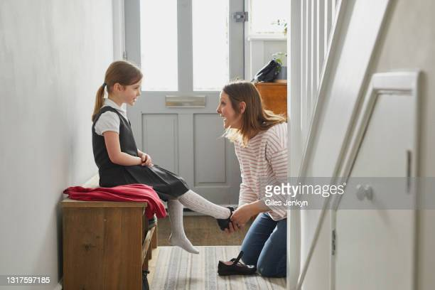 mother helping daughter put shoes on - footwear stock pictures, royalty-free photos & images