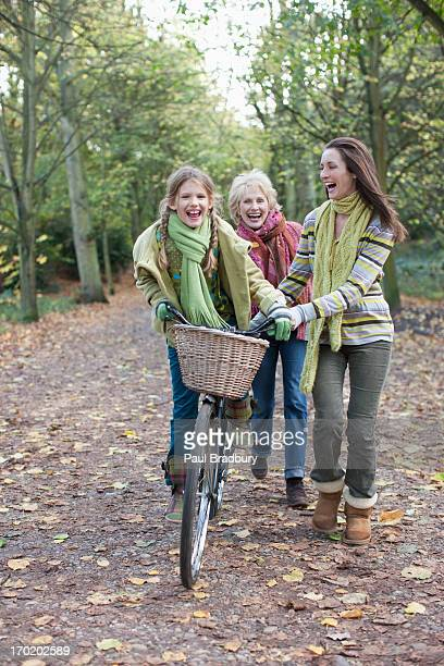 Mother helping daughter ride bicycle